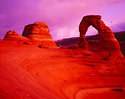 Volcanic dust in upper atmosphere from eruption of Mount Pinatubo casting warm dusk glow on Delicate Arch, Arches National Park, Utah.