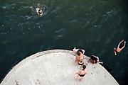 Nederland, Nijmegen, 25-6-2020 Mensen trekken massaal naar de oevers van de waal en de spiegelwaal in het rivierpark aan de overkant van Nijmegen . De warmte, hoge temperatuur, drijft mensen naar het water . Duiken vanaf een brugpijler . Het is verboden in de rivier te zwemmen vanwege de stroming het het drukke scheepvaartverkeer . . Foto: Flip Franssen
