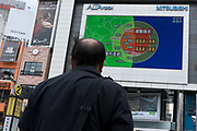 People watch video screens for news after a magnitude 9 earthquake and large tsunami hit the Tohoku region of north east Japan  on March 11th killing nearly 20,000 people and causing massive destruction along the whole coast, and a melt-down at the Fukushima Daichi nuclear power station. Shinjuku, Tokyo, Japan March 16th 2011