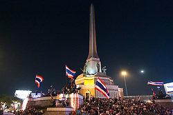 © Licensed to London News Pictures. 05/01/2014. Anti-government protestors wave Thai flags from the top of the Victory Monument at a rally during the third day of the 'Bangkok Shutdown' as anti-government protesters continue with their 'shutdown' of Bangkok.  Major intersections in the heart of the city have been blocked in their campaign to oust Prime Minister Yingluck Shinawatra and her government in Bangkok, Thailand. Photo credit : Asanka Brendon Ratnayake/LNP