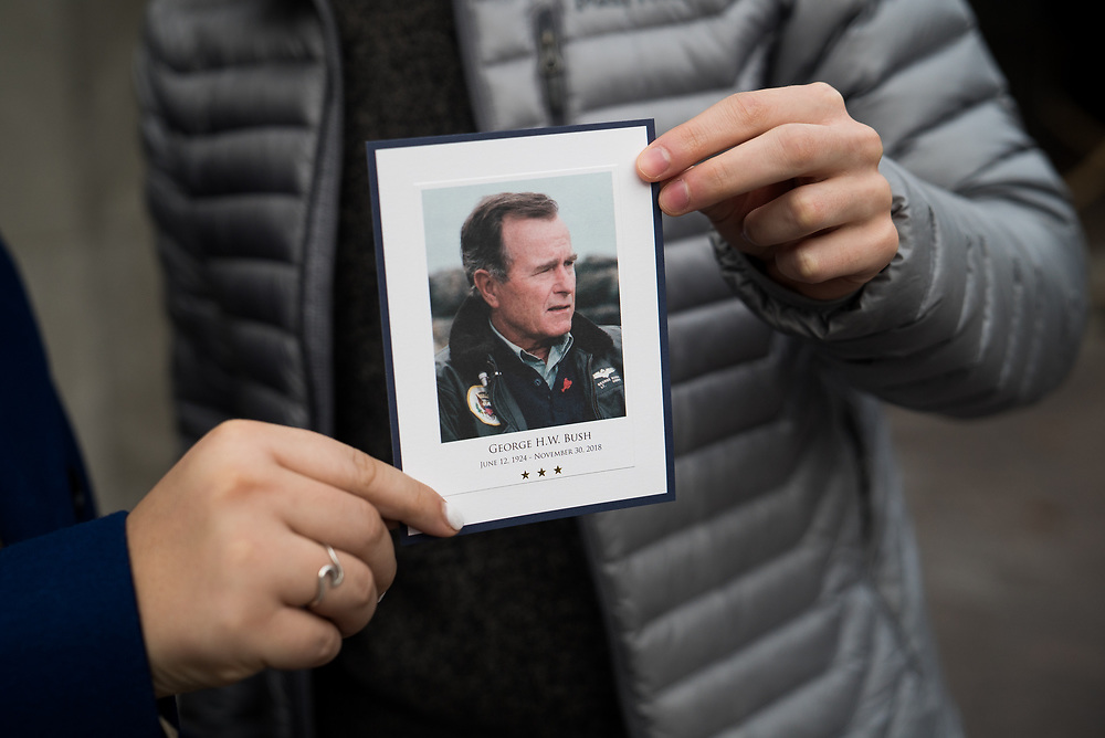 Yuri Nesen, 19, and Grace Rector, 19, both sophomores at Georgetown University, hold up a card commemorating former President George H.W. Bush after visiting his casket at the U.S. Capitol.