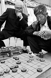 Men playing chequers in a Beijing hutong in China