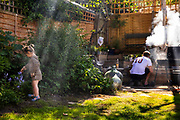 Family barbecue in garden with small child studying the flowers on 30th May, 2021 in London, United Kingdom.