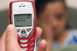 Child holding a mobile phone with bullying text message,