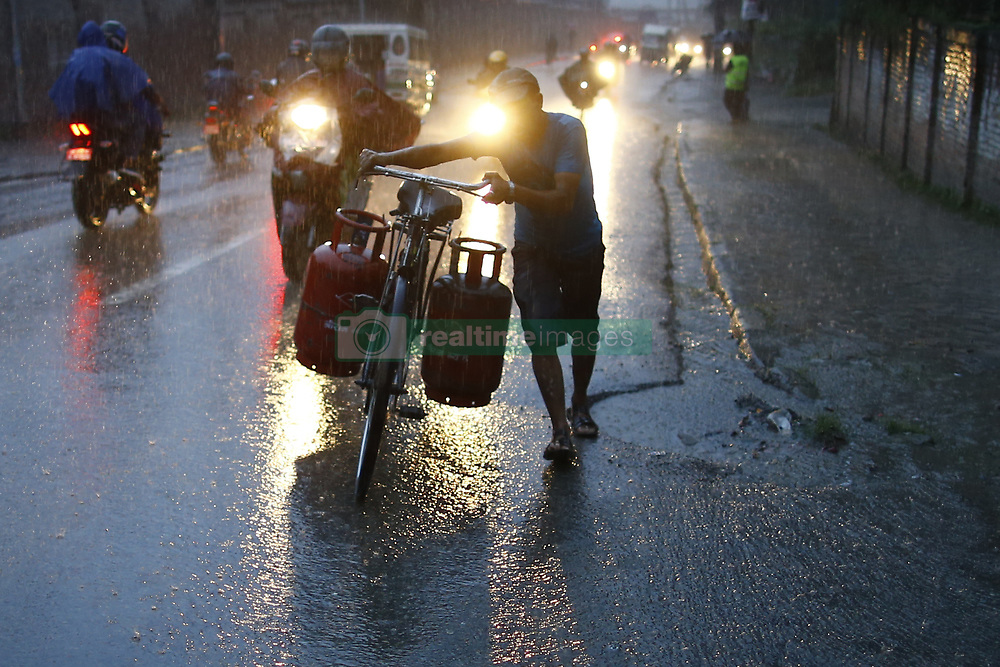 August 22, 2017 - Kathmandu, Nepal - A man rides his bicycle carrying cooking gas cylinders passing along a street during heavy rainfall in Kathmandu, Nepal on Tuesday, August 22, 2017. (Credit Image: © Skanda Gautam via ZUMA Wire)