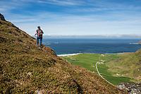 Female hiker on trail to Mannen with Uttakleiv in background, Vestvågøy, Lofoten Islands, Norway