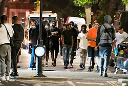© Licensed to London News Pictures. 26/06/2020. London, UK. Revellers loiter in the streets after police disperse an illegal Street Party at Riverton Close in Maida Vale, West London.  A number of similar events have occurred across the capital, with some resulting in violence towards police. Photo credit: Ben Cawthra/LNP