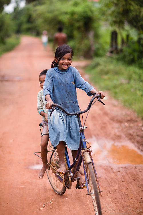 A girl on a bicycle with a young boy riding pillion along a muddy, rural road, Kampong Chhnang, Tonle Sap, Cambodia