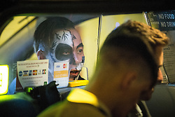 © Licensed to London News Pictures . 01/11/2015 . Manchester , UK . A cabbie wearing Halloween face makeup speaks to his passengers . Halloween revellers , wearing make up and costumes , out and about in Manchester City Centre . Photo credit : Joel Goodman/LNP