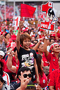 01 JULY 2011 - BANGKOK, THAILAND:  A boy waves a red flag, the symbol of the Red Shirts and Pheua Thai, during a Pheua Thai rally in Bangkok Friday. Thailand's divisive election campaign drew to a close Friday in Bangkok. Most of the parties had large rallies in an effort to sway last minute undecided voters. Pheua Thai, the party of ousted Prime Minister Thaksin Shinawatra held a massive rally in Rajamakala Stadium (also called Ramkamhaeng Stadium) to close out their campaign. A monsoon thunderstorm didn't keep people away from the event. Most Thai public opinion polls show Pheua Thai with a healthy lead over their arch rivals (and incumbent party in power) the Democrats. Thaksin's youngest sister, Yingluck Shinawatra, is running for Prime Minister under the Pheua Thai banner. If elected, she will be Thailand's first female Prime Minister.      PHOTO BY JACK KURTZ