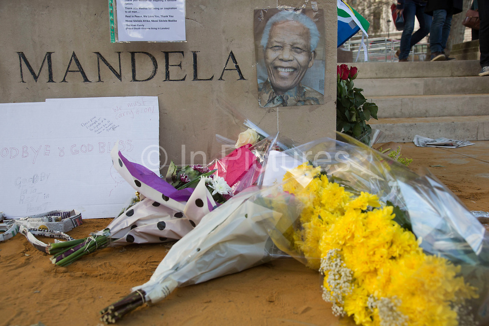 London, UK 6th December 2013: Flowers and notes in Parliament Square to pay tribute at the statue to former South African leader and anti-apartheid ANC campaigner Nelson Mandela, who died aged 95 on 5th December 2013.