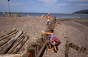 A partner struggles to lift a lady on a shingle beach up over a coastal groyne in Porlock, Somerset, UK. Giving the lady a much-needed leg-up from the lower level of shingle to the one above, the man bends to haul her up making a funny moment in this coastal landscape. Porlock is a coastal village and civil parish in Somerset, England, situated in a deep hollow below Exmoor, 5 miles (8 km) west of Minehead. The parish, which includes Hawkcombe and Doverhay, has a population of 1,440. The coastline includes shingle ridges, salt marshes and a submerged forest. In 1052 the Saxon king, Harold, landed at Porlock Bay from Ireland, and burnt the town before marching on London