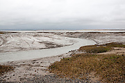 Muddy channel of the River Brue at low tide near its mouth at Burnham on Sea, Somerset, England