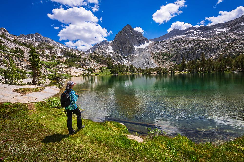 Hiker on the shore of Treasure Lake, John Muir Wilderness, Sierra Nevada Mountains, California USA