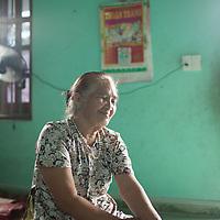 Van Thi Cúc at home in her living room with her daughter and grandson in Thủy Phư commune near Phú Bài town in Thừa Thiên–Huế province, Vietnam.