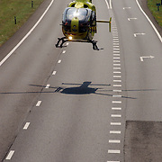 NLD/Blaricum/20050711 - Gekantelde vrachtwagen met gewonde chauffeur snelweg A27 ter hoogte Blaricum, traumaheli land op de snelweg.helicopter