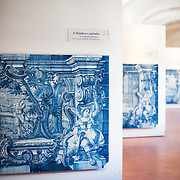 LISBON, Portugal - An exhibit of allegory panels of glazed tiles. The one in the front depicts the story of the Forest and the Woodcutter. The Monastery of São Vicente de Fora is a 17th-century church and monastery in the Alfama neighborhood of Lisbon. It features ornately decorated sections in the Baroque style as well as the Braganza Pantheon, where the kings who ruled Portugal between 1640 and 1910 are interred.
