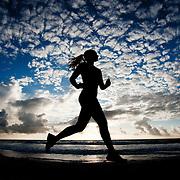 Woman running on the beach at sunrise.