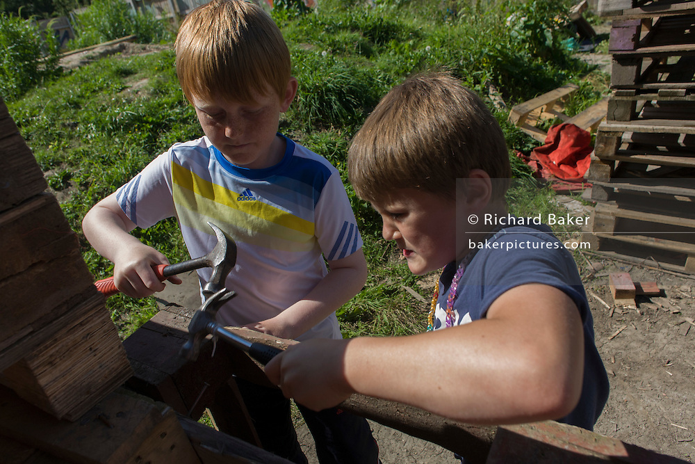 Boys use claw hammers in risk averse playground called The Land on Plas Madoc Estate, Ruabon, Wrexham, Wales.