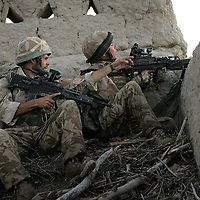 8th July 2007.Kajaki, helmand Province, Afghanistan.Lance Corpora Andrew Howe (27) (at left) points out a suspected taliban position as soldiers of 1 Royal Anglian C Coy move through a series of compounds at first light searching them in order to flush out Taliban fighters who have been using the locations as firing positions. The enemy were spotted and a sporadic firefight ensued. Kajaki, Helmand Province, Afghanistan, 8th July 2007.
