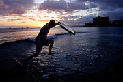 Surfer with boogie-board jumps into surf at sunset.<br /> Waikiki, Honolulu, Hawaii