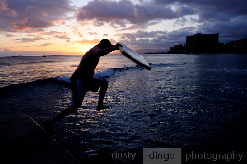 Surfer with boogie-board jumps into surf at sunset.<br /> Waikiki, Honolulu, Hawaii