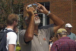 August 21, 2017 - College Park, MD, U.S - One of the people who assembled to view the solar eclipse outside the Physical Sciences Complex at the University of Maryland in College Park, seen using a pair of eclipse viewing glasses in front of his smartphone. (Credit Image: © Evan Golub via ZUMA Wire)