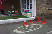 An incongruously silly village landscape at the site of a former post office-turned art gallery in Dulwich Village, south London on 30th May 2016. Traffic cones circle road markings in front of some Astroturf and a collection of a garden table and chairs.