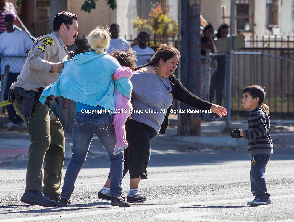 A Los Angeles County sheriff officer tries to stop the family members of the suspect running cross the tape line after   a suspected car burglar was wheeled out of a market on a gurney on Wednesday November 6, 2013 in Los Angeles, California. A suspected car burglar who apparently broke into a Florence-area market through a skylight hid from sheriff's deputies for several hours today until law enforcement officers went in to get him. (Photo by Ringo Chiu/PHOTOFORMULA.com)