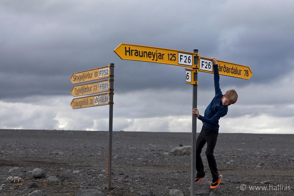 Young boy hanging in a waypoint in the highlands of Iceland - Skilti, vegvísar á Sprengisandsleið, Jurjen Sindri Sigurðarson