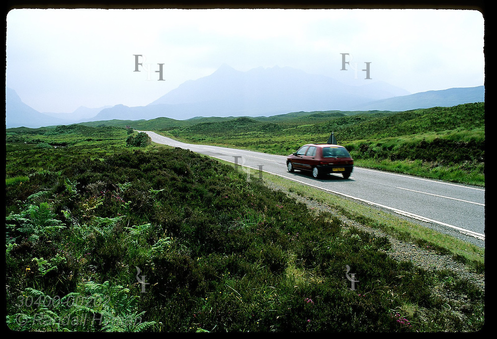 Car speeds along highway toward distant mountains on a stormy summer day; Isle of Skye. Scotland