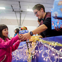 Layla Hooee, left, receives a gift from Andrea Pepin during the Toys for Tots event at the Zuni Wellness Center in Zuni Thursday.