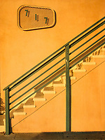 Yellow stucco wall with stairs and a green railing.