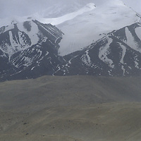 A Khyrgiz nomad leads his Bactrian camels below 7546-meter Mustagh Ata in the Pamir Mountains of Xinjiang, China.
