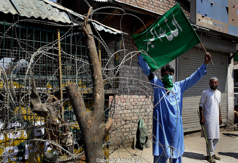 On the 22nd August 2008 an estimated 350,000 Kashmiri's marched to the Eidgha communal ground in Srinagar demanding Independence from India. Local Kashmiri's said they had never witnessed anything like it in their lifetime. .A pro Independence protester waves a Kashmiri flag next to an Indian army check point....