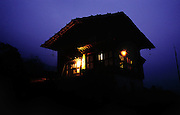 Electricity comes to the Bhutanese village of Shingkhey in 2001. The view of Namgay and Nalim's house lit with electricity for the first time, Shingkhey, Bhutan. Now, even the cows have a nightlight.