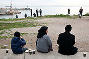 Greece . Chios Island, one of the places where refugees from Turkey land en route to Northern Europe. Newly arrived refugees relax on the beach next to Souda camp where they have to register. Turkey is visible in the distance.
