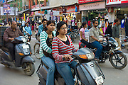 Young Indian girls ride motor scooter in street scene in city of Varanasi, Benares, Northern India