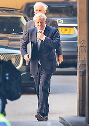 © Licensed to London News Pictures. 25/07/2019. London, UK. Prime Minister Boris Johnson straightens his tie as he arrives at Parliament with Sir Edward Lister his Chief of staff after holding his first Cabinet meeting in Downing Street. The Conservative Party has elected Boris Johnson as their new leader and Prime Minister, following Theresa May's resignation. Photo credit: Peter Macdiarmid/LNP