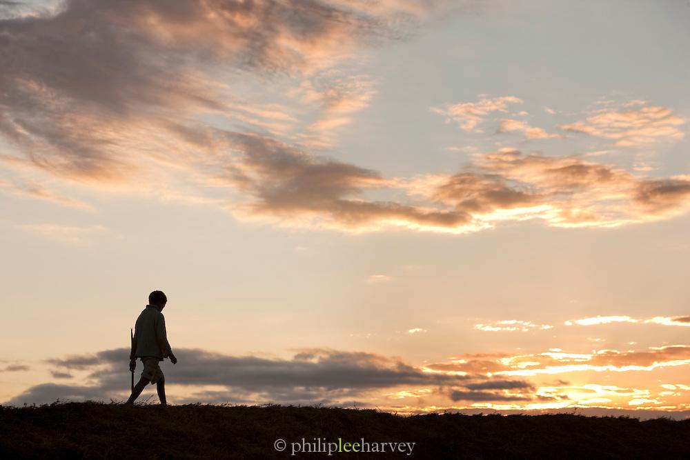 Young boy walking along a river bank in the capital city Antananarivo, Madagascar