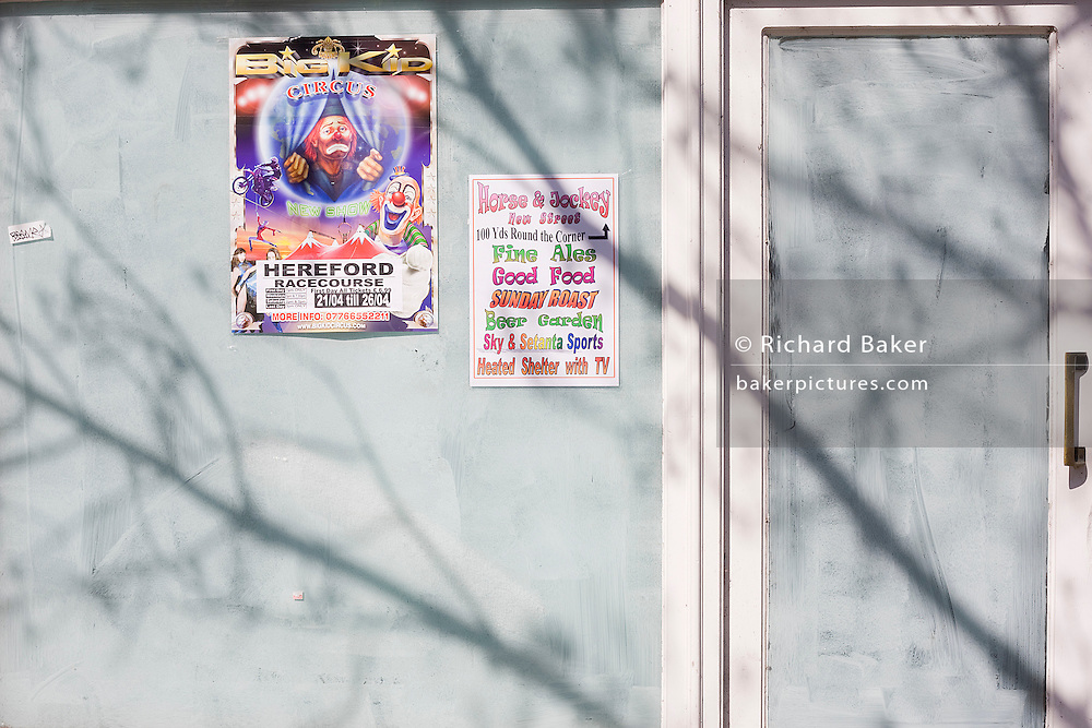 The sad face of a clown is seen on a circus poster next to a local pub advert that are pasted on a former high street business window in the border town of  Ross-on-Wye, a victim of the UK economic recession.