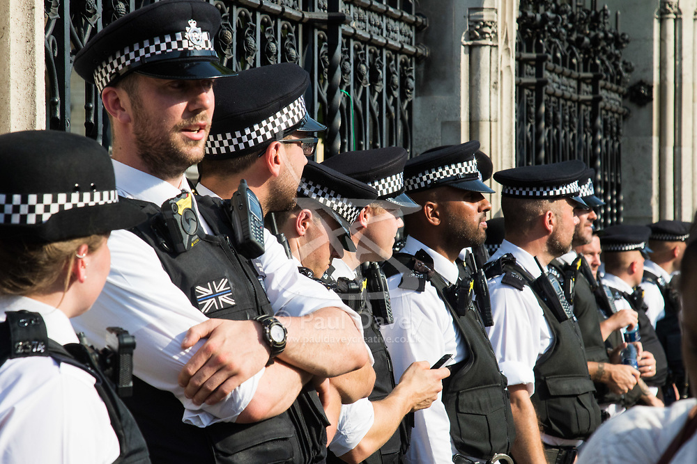 London, June 21st 2017. Protesters march through London from Sheherd's Bush Green in what the organisers call 'A Day Of Rage' in the wake of the Grenfell Tower fire disaster. The march is organised by the Movement for Justice By Any Means Necessary and coincides with the Queen's Speech at Parliament, the destination. PICTURED: Police officers rest against the railings of the Palace of Westminster.