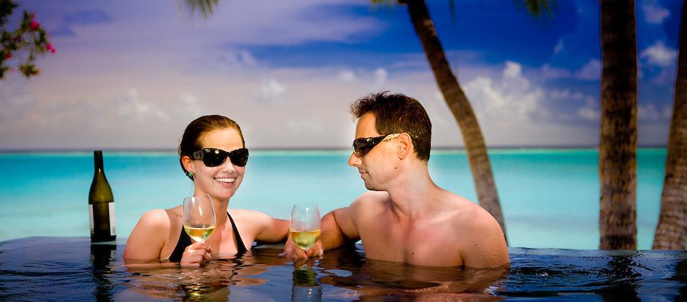 Romantic Couple wearing Sunglasses Enjoy Wine in Infinity Pool Facing the Beach and Ocean, Fiji