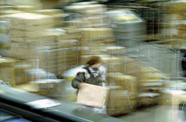 Nederland, Maastricht, 15-1-2006Een medewerker van een koeriersbedrijf op maastricht airport sorteert vracht, paketten, die uit een vliegtuig op vliegveld, luchthaven, airport maastricht, aachen aangevoerd zijn. Vrachtvervoer door de lucht, luchtvracht, transport, economie, milieu, koeriersbedrijf, kosten, magazijn.Foto: Flip Franssen/Hollandse Hoogte