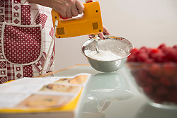 Senior woman mixing meringue in mixing bowl in kitchen, Munich, Bavaria, Germany