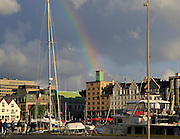 Rainbow over sailing yachts and historic buildings evening light, Vagen harbour, Bergen, Norway