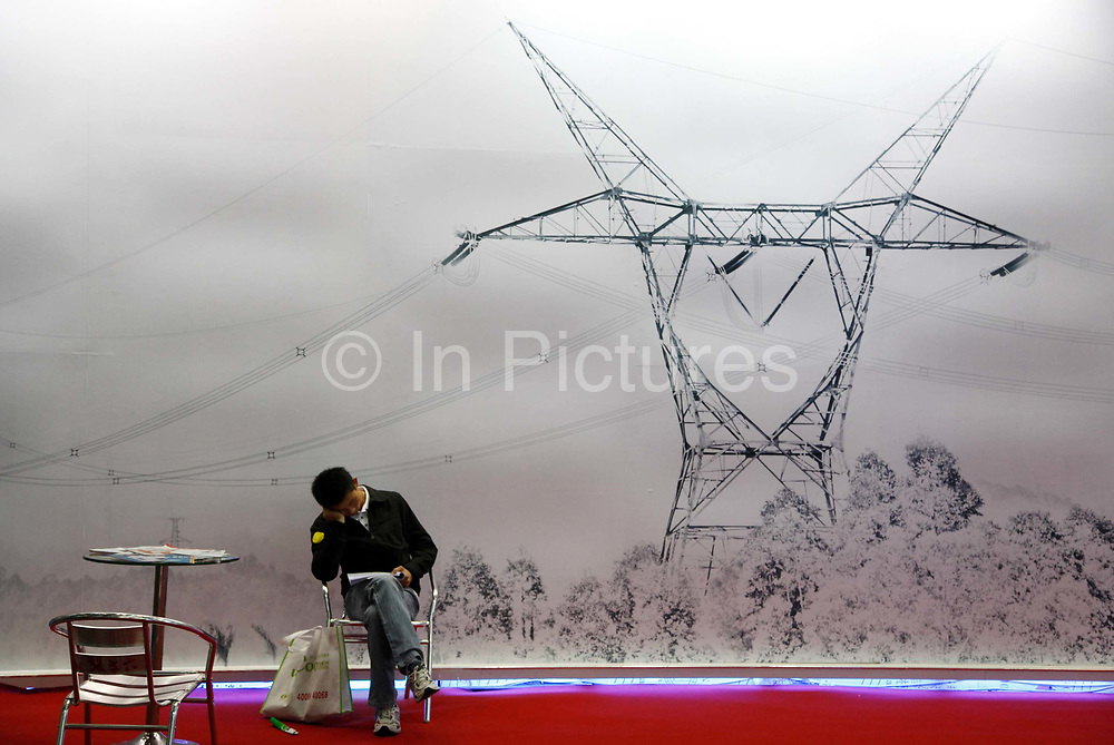 """A visitor takes a rest while sitting beside a poster showing high-tension power lines at a technology fair in Shenzhen, Guangdong Province, China on 17 November 2009. China is heavily investing in its solar power sector as it announced that the government has decided to subsidize 294 solar power plants which will generate 642 megawatts of power. The subsidies are part of China's """"golden sun"""" plan, a project meant to find alternative energy sources."""