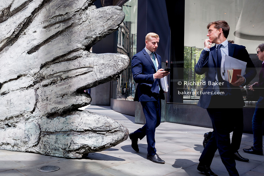 City businessmen walk past the sculpture entitled 'City Wing' on Threadneedle Street in the City of London, the capital's financial district, on 17th June 2019, in London, England. This ten-metre-tall bronze sculpture is by President of the Royal Academy of Arts, Christopher Le Brun, commissioned by Hammerson in 2009. 'The City Wing' and has been cast by Morris Singer Art Founders, reputedly the oldest fine art foundry in the world.