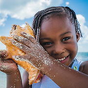 A young Bahamian girl plays with a conch shell on beach in Nassau, Bahamas. Conch are part of the cultural heritage of The Bahamas and other Caribbean nations. Their loss would be deeply felt.