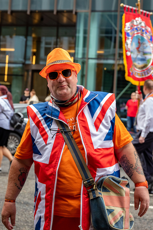 Onlooker dressed in orange and wearing the union jack in support of the Orange March, Belfast, NI,2021